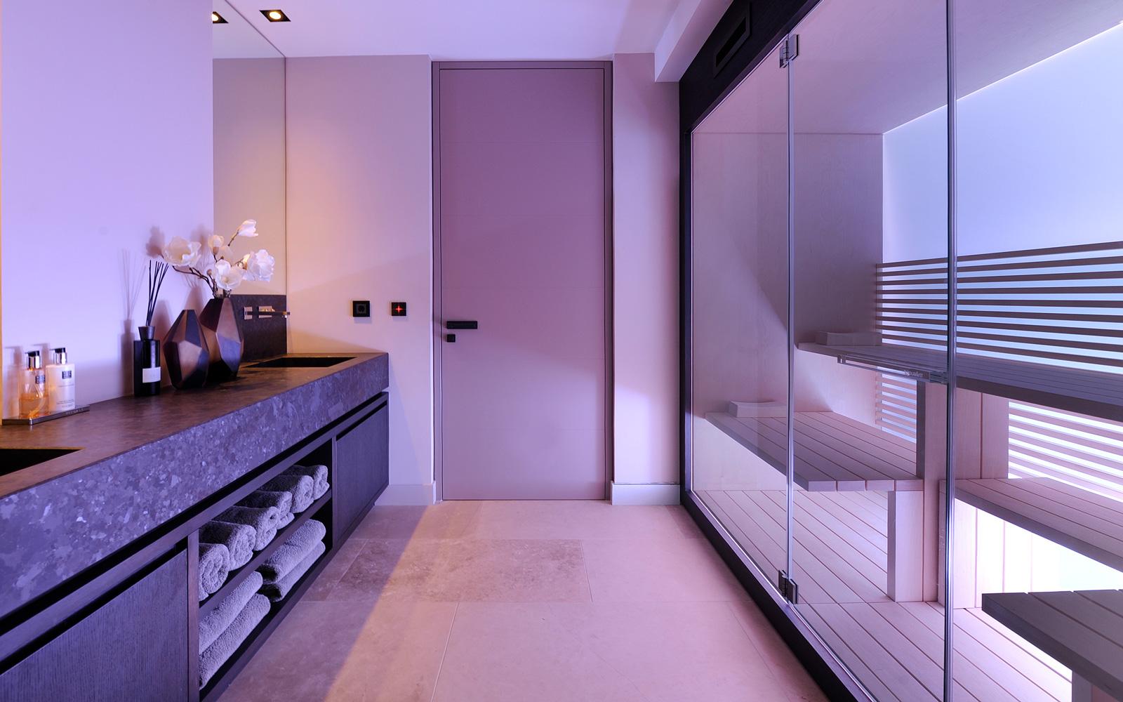 De sauna is afgewerkt met paarse led verlichting.