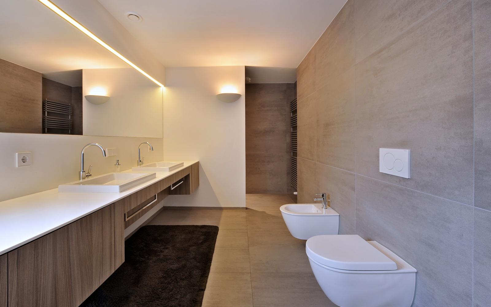 De villa beschikt over een ruime badkamer afgewerkt met witte bad meubelen.