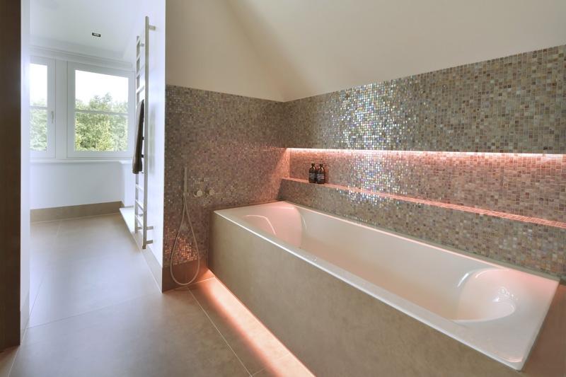 De exclusieve badkamer beschikt over een ruim ligbad met led verlichting.
