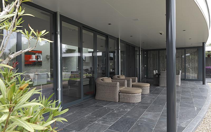 The Art of Living, Exclusief wonen, Overdekt terras, villa met uitzicht, Theunissen Schilderwerken, Bouwgroep van Stiphout, lounge stoelen, vloertrend, zwart, tuin