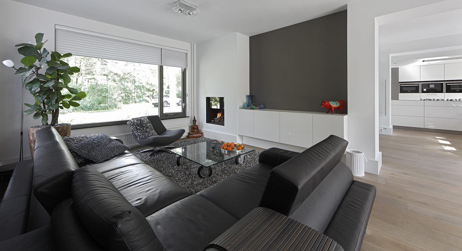 The Art of Living, Exclusief wonen, Bas Openhaarden, woonkamer, moderne bank, kunst, strak interieur, grote ramen, lichtinval, vloerkleed, laminaat, keuken, wit, bankstel