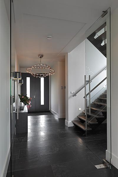 The Art of Living, Exclusief wonen, Ruimtelijke inkom, Koek Verlichting, Theunissen Schilderwerken, moderne trap, strak interieur, designlamp, glazen deuren, tegelvloer, glas