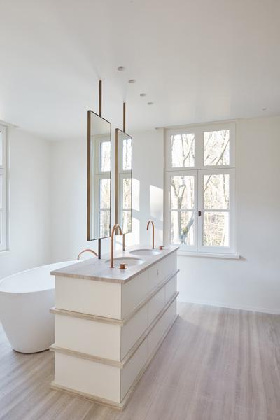 De badkamer is ruimtelijk ingericht met witte details.