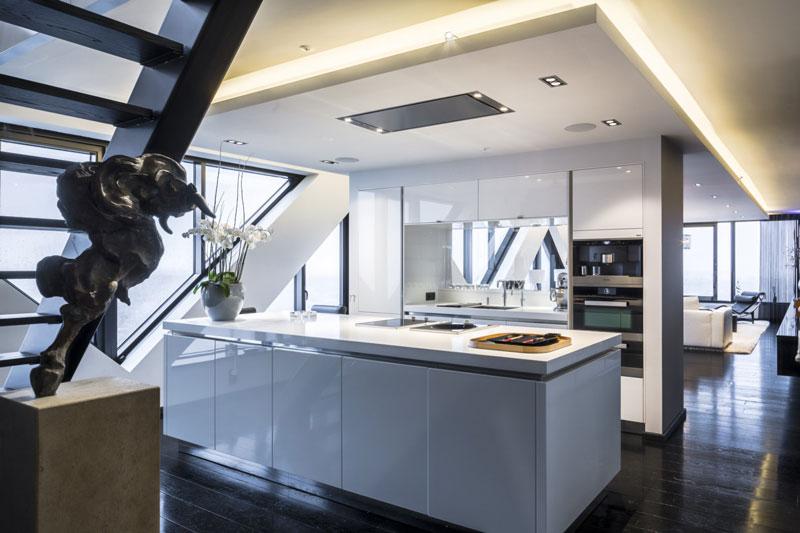 The Art of Living, Exclusief wonen, Bohemian works, Strakke witte design keuken Penthouse Babylon Residences, keuken, design, interieur, zwart laminaat, trap, kunst, keukenapparatuur, wit kookeiland