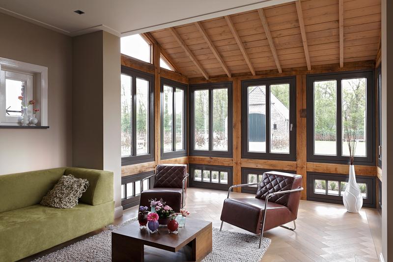 The Art of Living, Exclusief wonen, Ruimtelijke woonkamer, stalen deuren, stalen ramen, hout, De Kempen parketvloeren, zithoek, tapijt, laminaat, houten dak, lichtinval