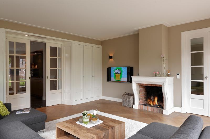 The Art of Living, Exclusief wonen, Moderne woonkamer, open haard, witte schuifdeuren, Bouwmans Vuur Totaal, J. Verheggen elektrotechniek, laminaat, strakke inrichting, klassiek