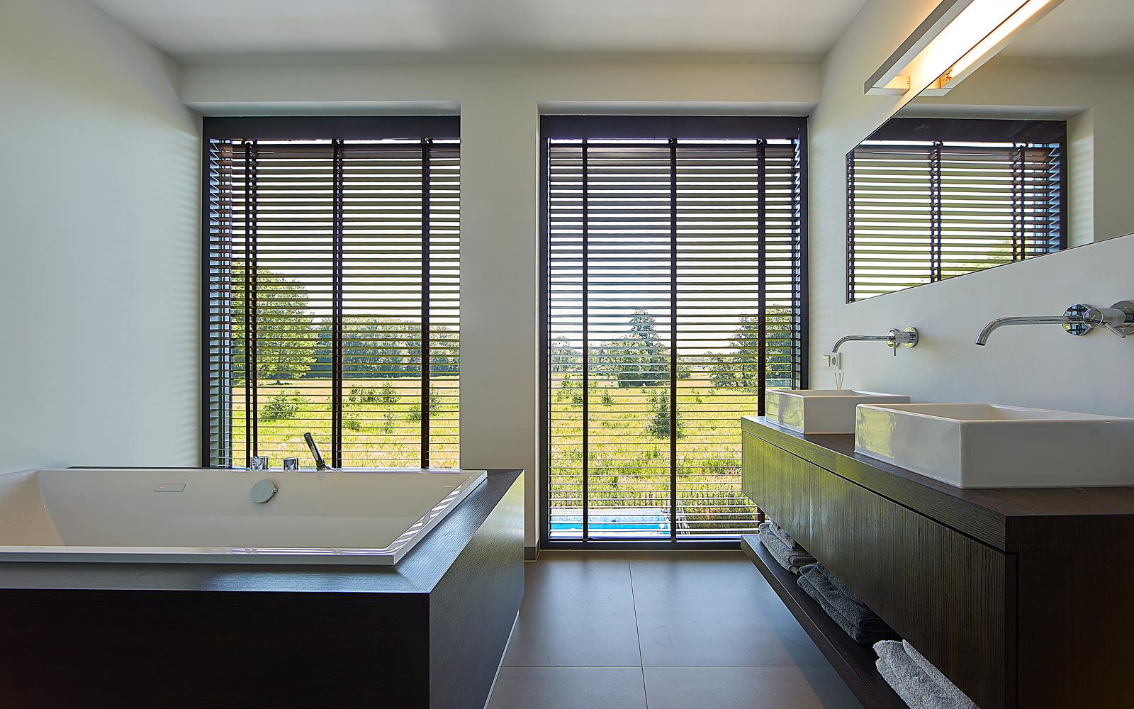 De badkamer is voorzien van luxe bad meubelen op een donkere tegelvloer.