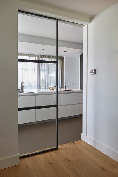 De exclusieve glazen schuifdeur staat mooi op de houten vloer.