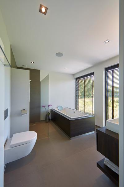 De luxe badkamer beschikt over een ligbad en een inloopdouche.