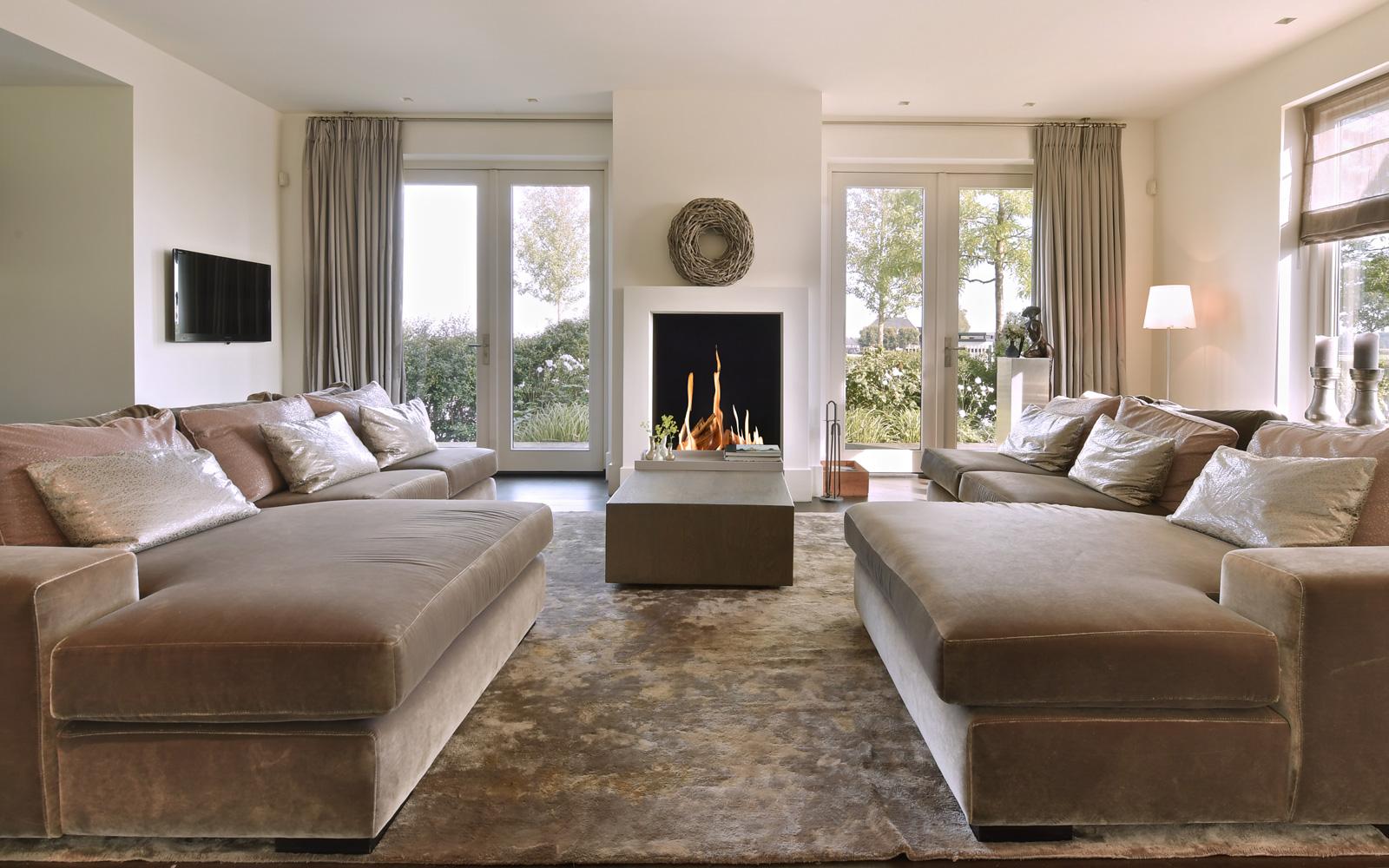 De luxe banken in combinatie met de open haard zorgen voor een mooi design.