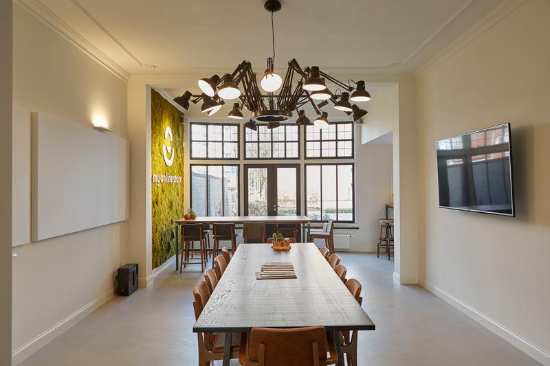 De designverlichting staat mooi boven de houten eettafel.