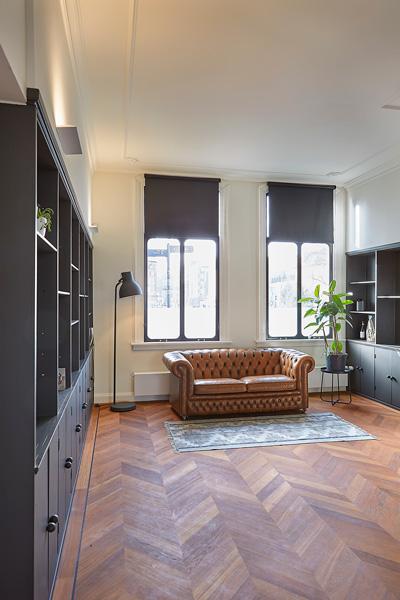 De bruine bank staat mooi op de houten vloer.