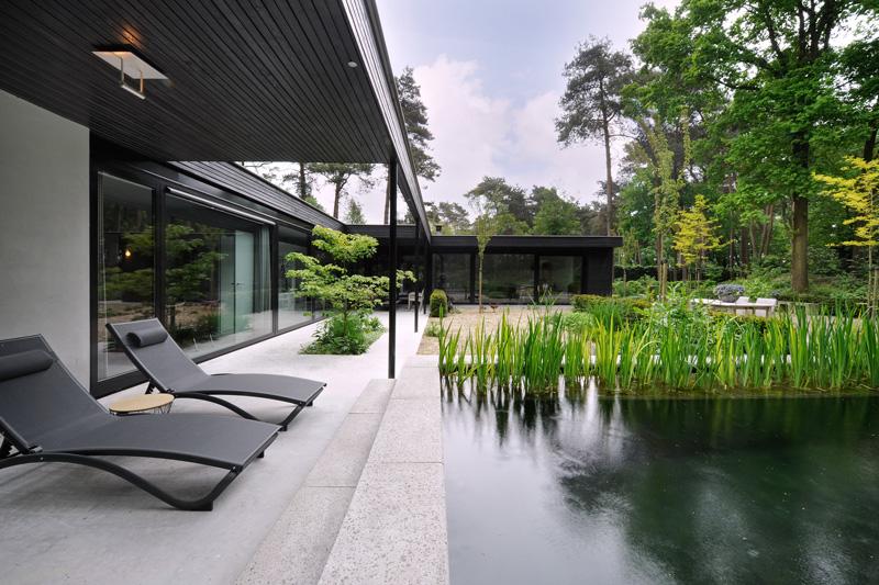 Naast de zwemvijver staan luxe stoelen voor het optimale comfort.