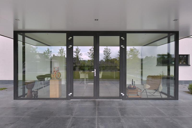 Vanuit de woonkamer kan men direct de tuin inlopen door een stalen deur.