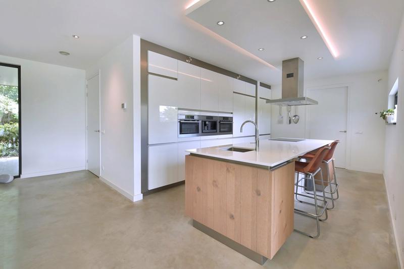 De luxe witte keuken biedt genoeg ruimte.