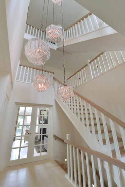 De designverlichting past mooi bij het witte trappenhuis.