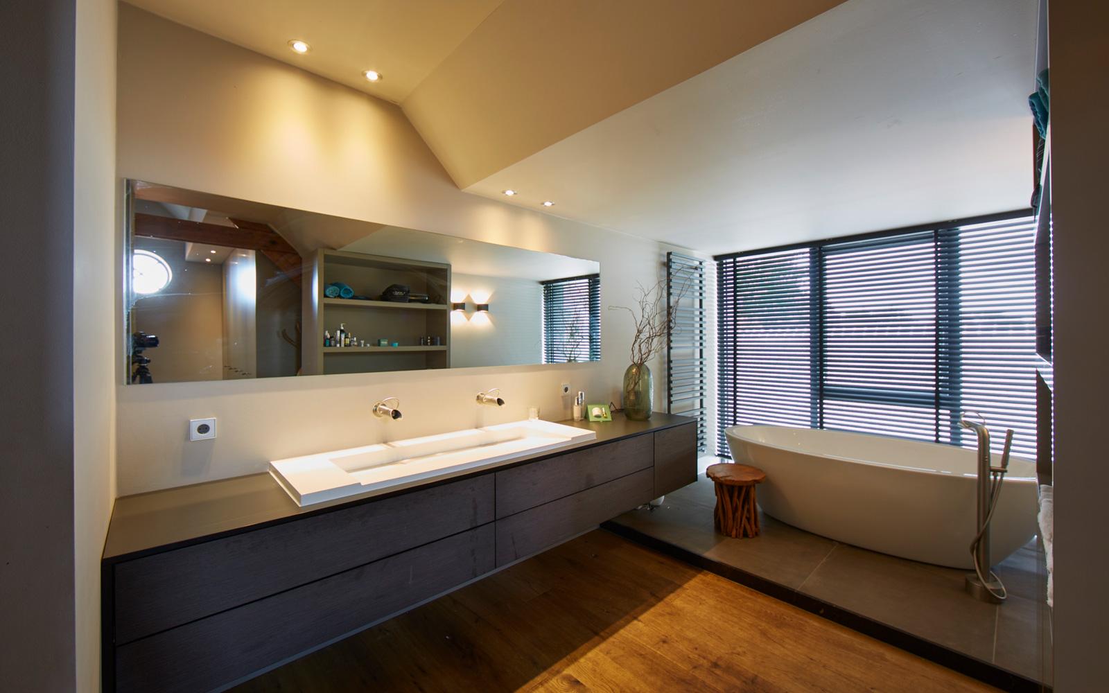 De moderne badkamer is voorzien van een grote wastafel en een vrijstaand ligbad.