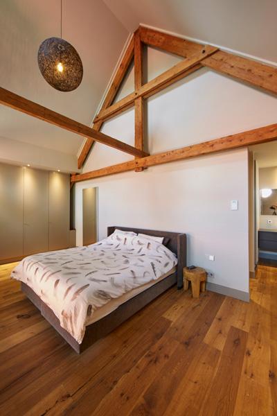 De grote slaapkamer geeft een ruimtelijk gevoel door de houten vloer.