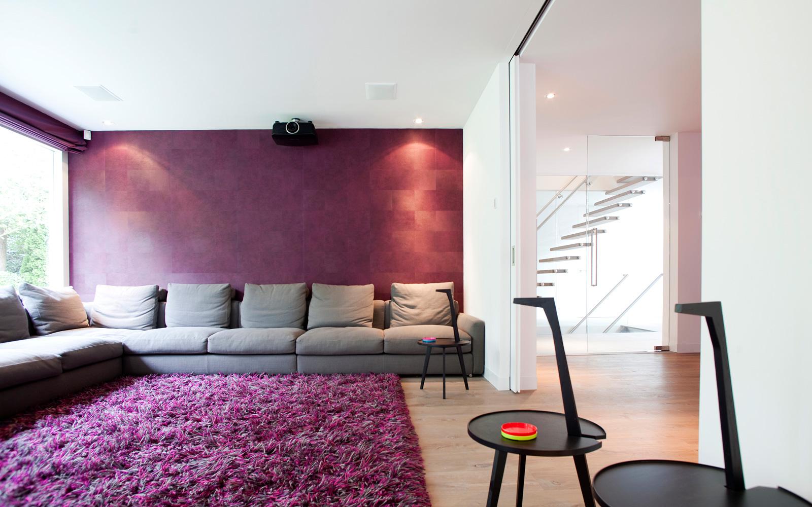 De luxe grijze bank staat mooi op de paarse wand en het vloerkleed.