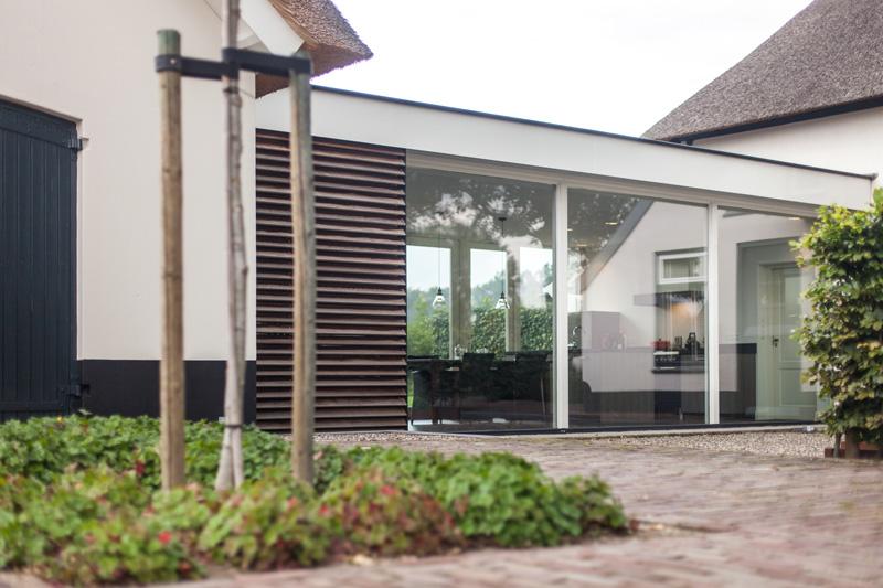 Het tussenstuk tussen de woningen bestaat voor een groot deel uit een glazen wand.
