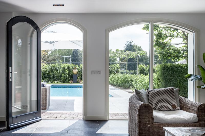 De stijlvolle woonkamer kijkt uit op de luxe tuin.