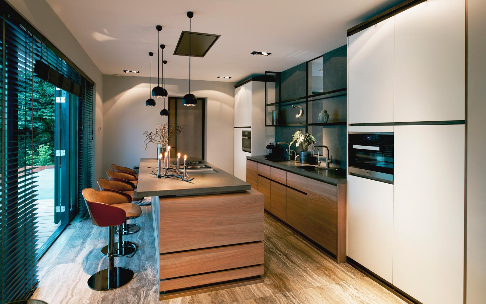 De keuken heeft een robuuste en tegelijk luxueuze uitstraling dankzij de vormgeving en de combinatie van basaltsteen en olijfhout