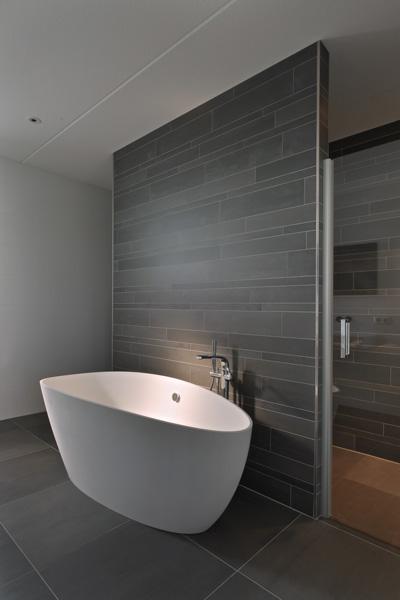 Het vrijstaande witte ligbad past perfect op de donkere tegelvloer.