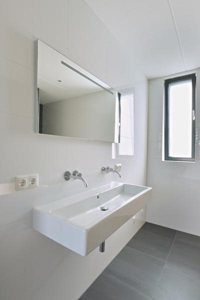 De badkamer is voorzien van een hangende wastafel onder een grote spiegel.