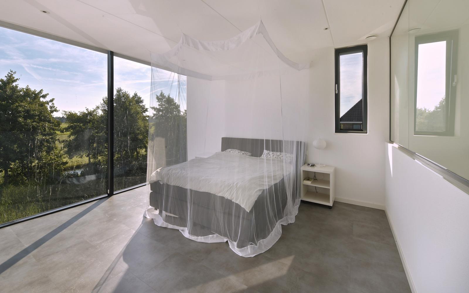 De masterbedroom heeft een grote glazen wand die zorgt voor ruimte en lichtinval.