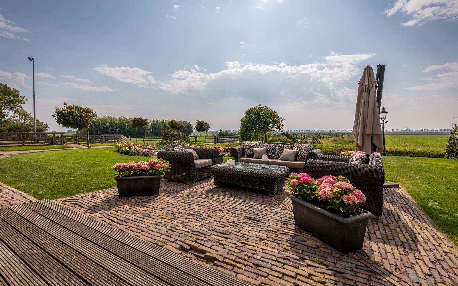 De grote landelijke tuin is ingericht met een loungeset.