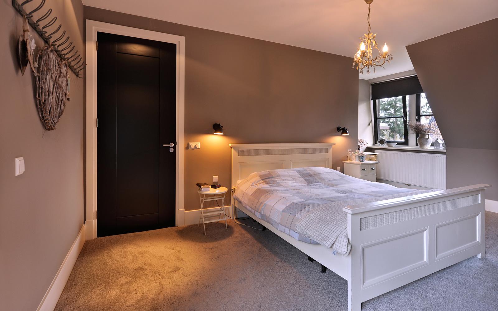 De slaapkamer aangekleed met kunst en designverlichting.