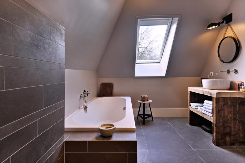 Ruim ingerichte badkamer met perfectionistisch tegelwerk.