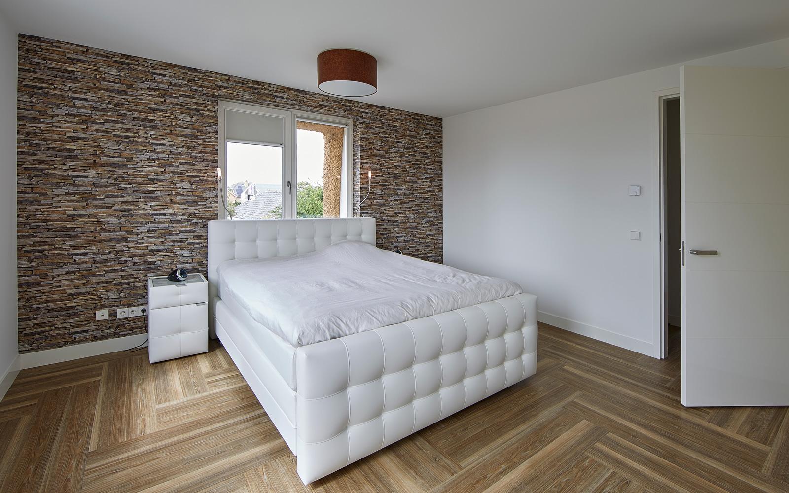 De designwand combineert perfect me het witte bed.