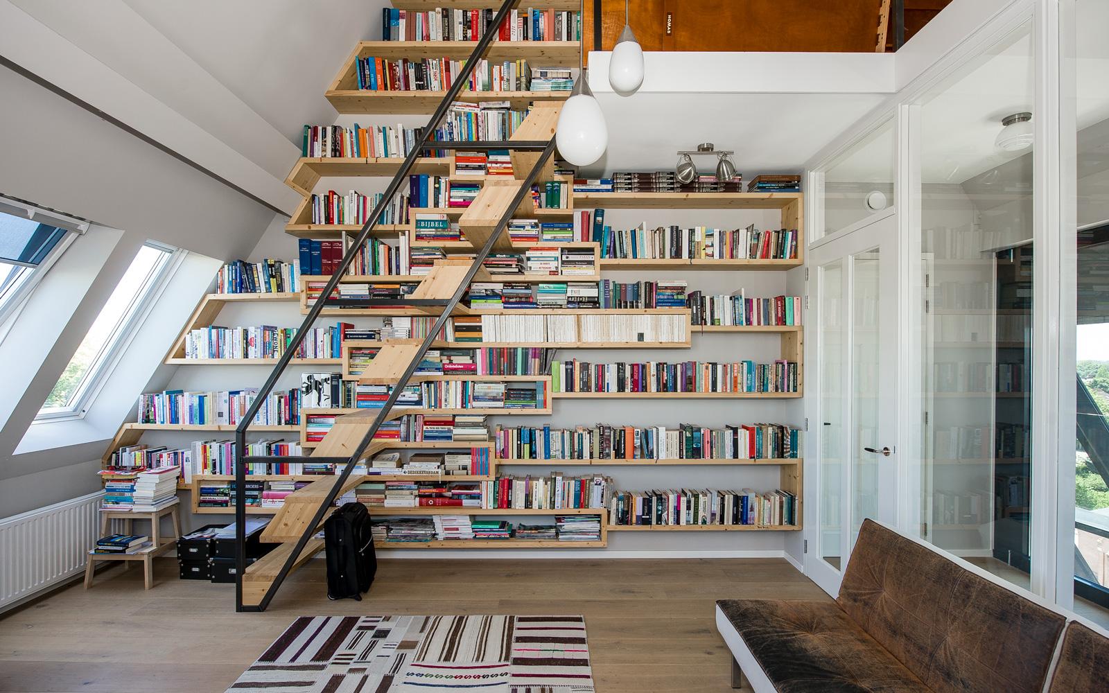 De op maat gemaakte boekenkast reikt tot aan het plafond.