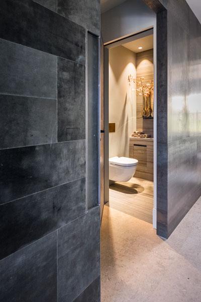 Natuurstenen vloer van Lenarduzzi, industriële look, blauwstaal, schuifdeur, toilet, showroom, architectenbureau Kabaz