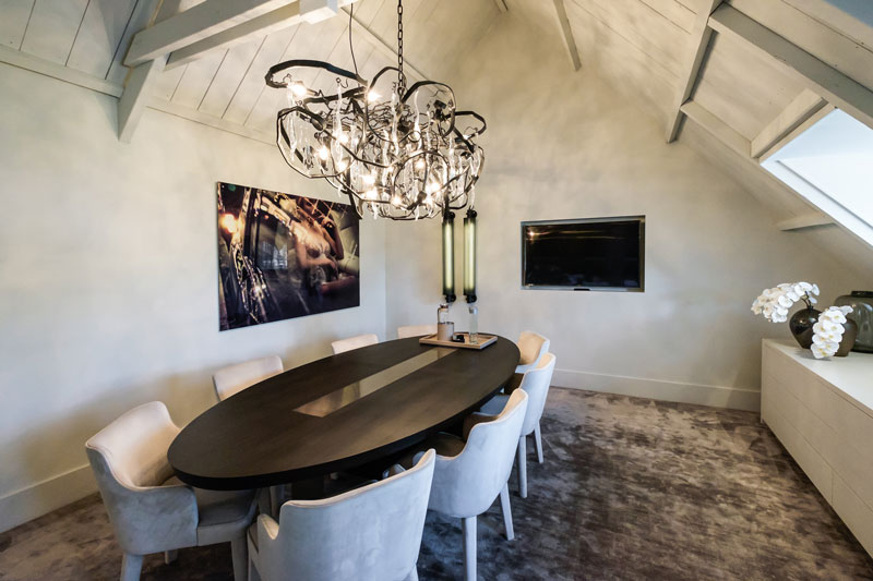 Grote ovalen tafel, designverlichting, televisie, tapijt, showroom, architectenbureau Kabaz