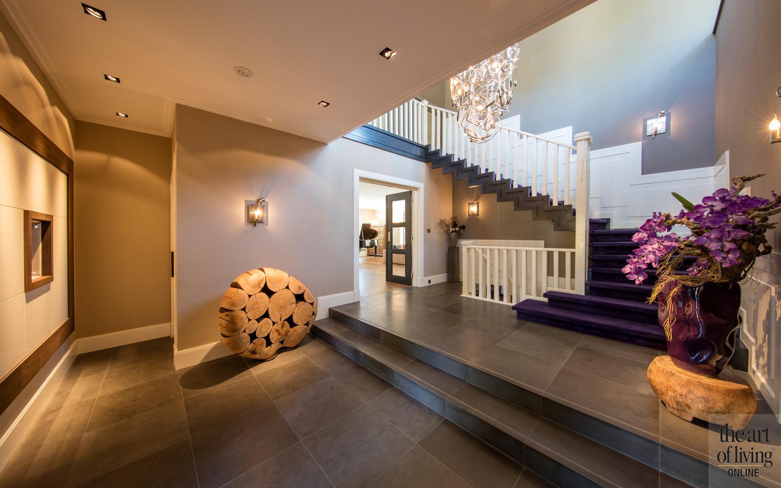 entree met strakke trap, en paarse loper en een Italiaanse kroonluchter, natuursteen tegels van KROON Projecten