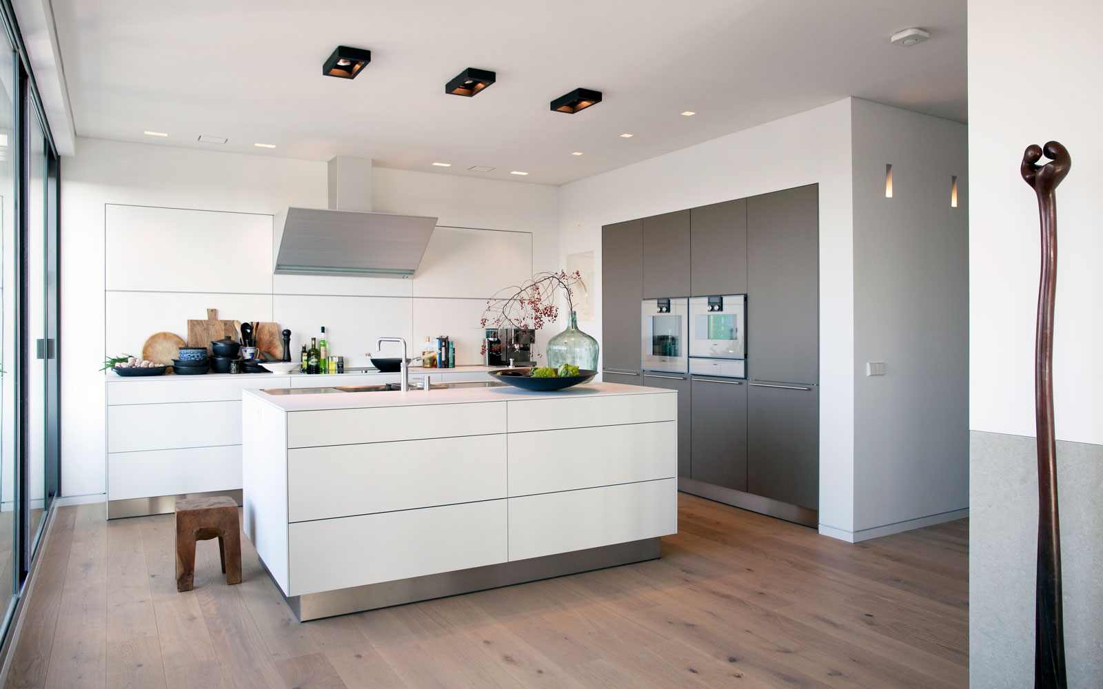 Strakke witte keuken door Bulthaup Leiden Keukenarchitectuur, rvs plinten, zwevende keuken, Penthouse Den Haag, Marco van Zal