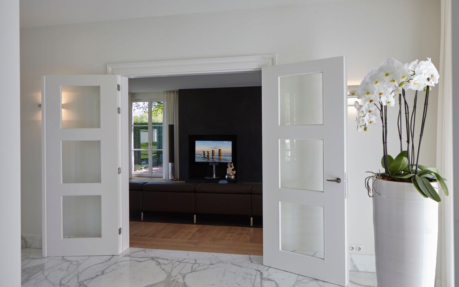 Hal, deuren naar de woonkamer, marmeren vloer, houten vloer, televisie Band & Olufsen, marmeren villa, Rob Zeelen Interior