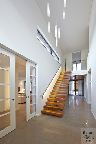 Hal met zwevende trap, houten trap, en suite deur