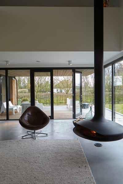 Woonkamer met haard van Boley, grote ramen, stalendeurenhuys, Landelijk, modern, Architectenbureau Koppens