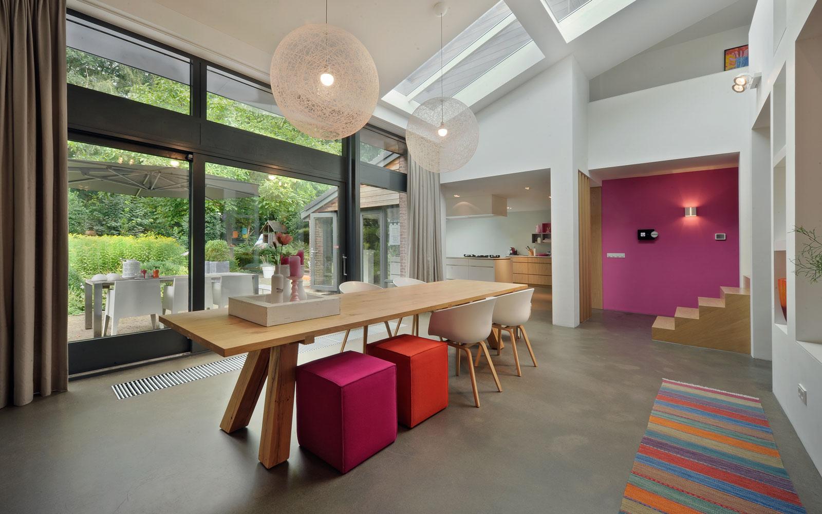 Ruime woonkamer, betonvloer, houten tafel, grote ramen, jaren 70 woning, De Bever Architecten