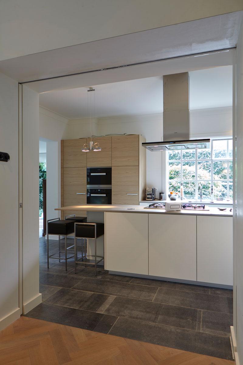 Keuken, wit, houten kasten, kookeiland, tegelvloer, natuursteen, Revy Stone, jaren 30 villa, renovatie, Marco Daverveld