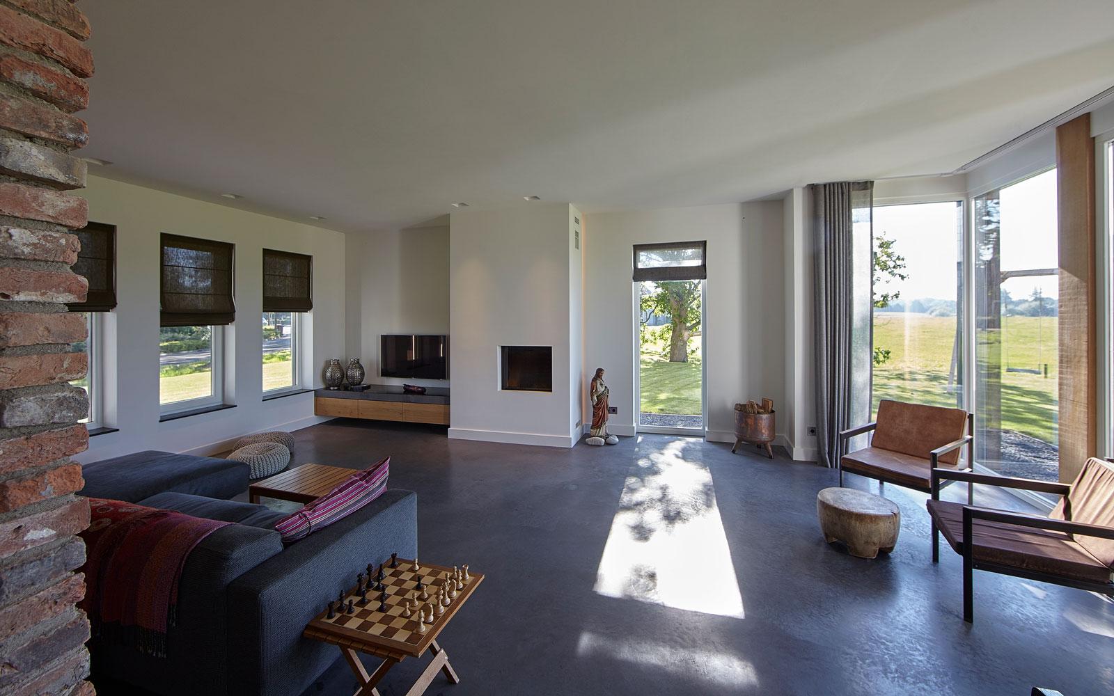 Ruime woonkamer, beton vloer, uitzicht, grote ramen, open haard, landelijk, industrieel, Wolfs Architecten