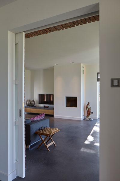 Doorkijk naar de woonkamer, betonvloer, open haard, en suite deur, schuifdeur, landelijk, industrieel, Wolfs Architecten