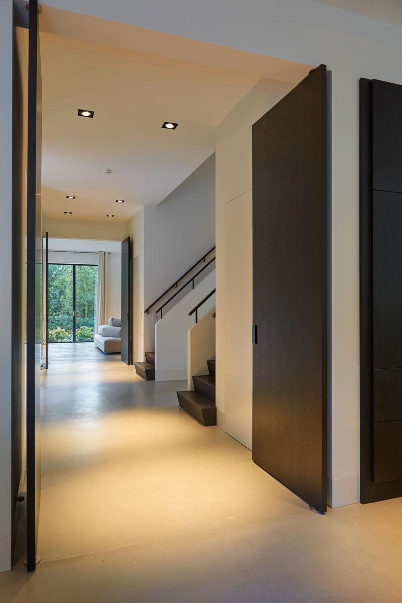 Hal, donkere taatsdeuren, zwart-wit, trap naar boven, symmetrische villa, PBV Architects