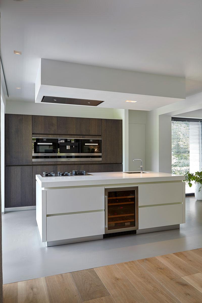 Keuken met wit kookeiland, betonvloer, houten vloer, scheiding, inspirerende villa, Wolfs Architecten