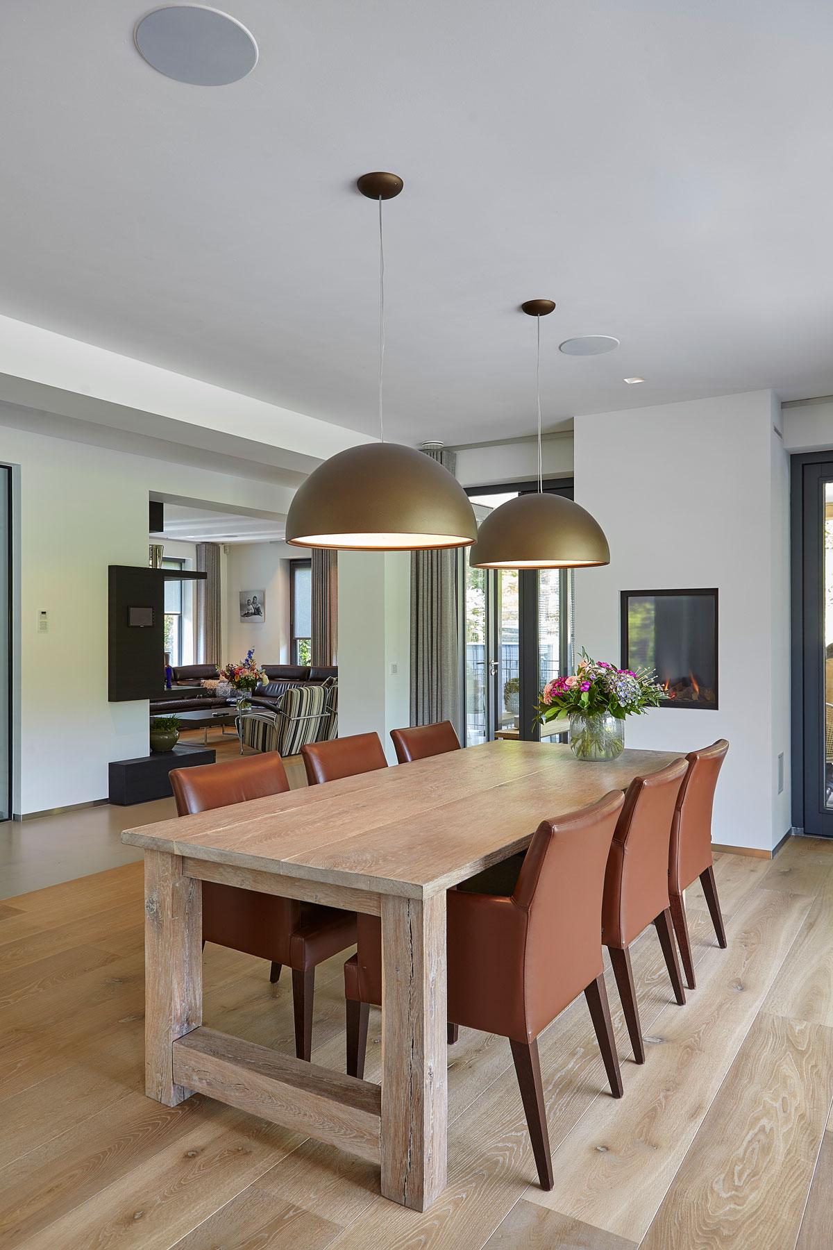 Eettafel met verlichting van Lichtstudio Kwadraat, houten vloer, haard, domotica van JNV, inspirerende villa, Wolfs Architecten