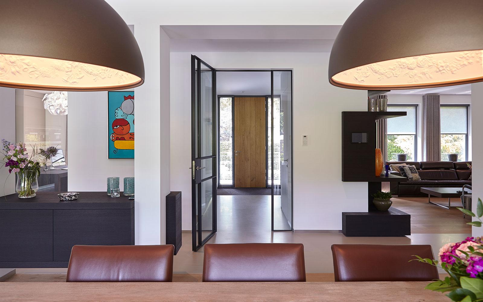 Eettafel met lampen van Lichtstudio Kwadraat, houten voordeur, entree, woonkamer, inspirerende villa, Wolfs Architecten