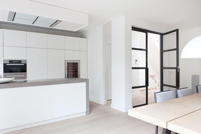 Eetkamer, keuken, houten vloer, houten tafel, strakke witte keuken, stadsvilla, Remy Meijers